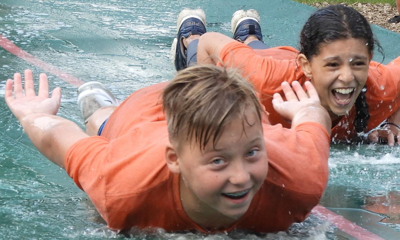 2 leerlingen die lachend glijden over de waterglijbaan