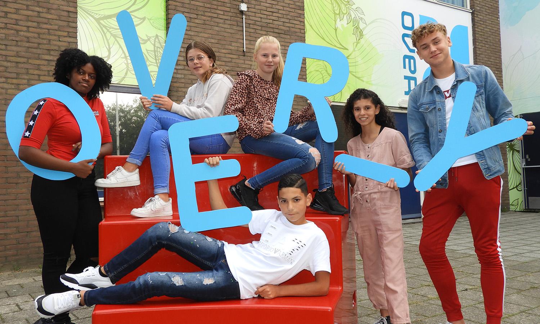 leerlingen voor het gebouw van het Over-Y college met elk een letter van de naam van de school